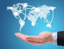 Mappa del globo della tenuta della mano dell'uomo d'affari isolata su fondo blu fotografia stock