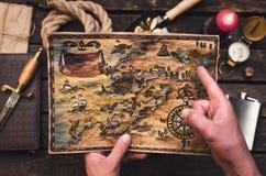 Mappa del tesoro in mani del cacciatore di tesoro fotografia stock
