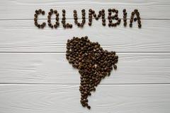 Mappa della Colombia fatta dei chicchi di caffè arrostiti che mettono su fondo strutturato di legno bianco Fotografia Stock
