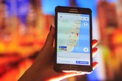 Mappa di Florida sul telefono nei precedenti di una città di notte Chiuda su del telefono cellulare della tenuta della mano della Fotografie Stock