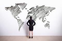 Mappa di mondo di sguardo della donna di affari immagini stock libere da diritti