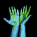 Mappa di mondo dipinta sulle mani umane Fotografie Stock Libere da Diritti