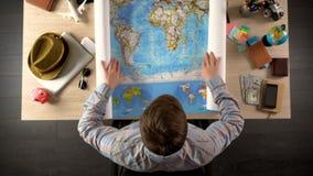 Mappa di mondo maschio di spiegamento per scegliere paese per la destinazione di viaggio, vacanza immagini stock
