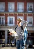 Mappa di sguardo turistica della città di giovane viaggiatore con zaino e sacco a pelo dello studente persa e sconcertante nella  Fotografie Stock Libere da Diritti
