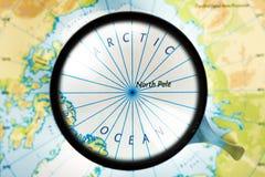 Mappa, lente d'ingrandimento e mare Glaciale Artico sul fuoco Fotografia Stock