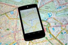 Mappe mobili moderne contro le mappe di carta tradizionali per navigazione Fotografia Stock Libera da Diritti