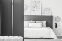 Maps in minimal hotel interior. Black screen in minimal hotel room interior with maps above bed next to a clock and table Stock Photo