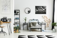 Maps in spacious boy`s room. With workspace and chair next to cabinet with plant and triangles Stock Image