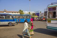 Indian girls in bright multi-colored sarees walk between the buses at the bus station. Mapusa,Goa,India - 20.12.2018 Indian girls in bright multi-colored sarees royalty free stock images