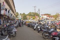 Indian motorcycle parking and walking people on the background of urban modern houses and green. Mapusa, Goa/India - 24.01.2019: Indian motorcycle parking and royalty free stock photos