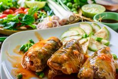 Maquereau avec la sauce tomate, les légumes et les herbes dans un plat sur la table Photos stock