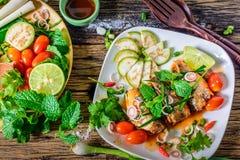 Maquereau avec la sauce tomate, les légumes et les herbes dans un plat sur la table Y Images libres de droits