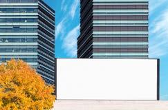 Maqueta al aire libre en blanco de la cartelera con los edificios modernos del negocio imagen de archivo