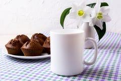 Maqueta blanca de la taza con los molletes del chocolate en la placa fotos de archivo