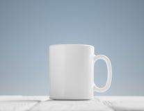 Maqueta blanca de la taza inclinada en la tabla de madera fotografía de archivo