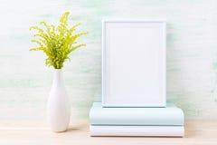 Maqueta blanca del marco con la hierba verde y los libros ornamentales fotos de archivo