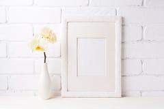 Maqueta blanca del marco con la orquídea amarilla suave en florero foto de archivo