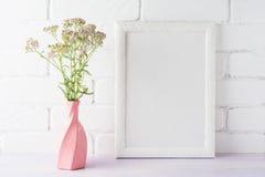 Maqueta blanca del marco con las flores rosadas cremosas en florero remolinado Fotos de archivo