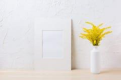 Maqueta blanca del marco de la estera con la hierba floreciente amarilla ornamental adentro Fotos de archivo