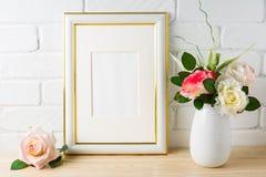 Maqueta blanca del marco en la pared de ladrillo con las rosas Fotos de archivo libres de regalías
