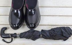 Maqueta Botas de goma negras con el paraguas en el fondo de madera blanco imágenes de archivo libres de regalías