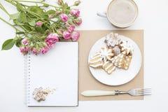 Maqueta con la libreta en blanco, la taza de café y pocas rosas del rosa de jardín Galletas y capuchino del Año Nuevo Navidad Imágenes de archivo libres de regalías
