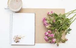 Maqueta con la libreta en blanco, la taza de café y pocas rosas del rosa de jardín Galletas y capuchino del Año Nuevo Navidad Imagenes de archivo
