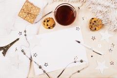 Maqueta con una taza de té, de tarjeta y de pluma en fondo de la tela fotografía de archivo