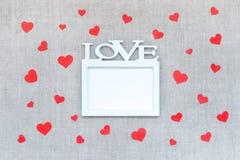 Maqueta de día de San Valentín con el marco blanco con la palabra AMOR y muchos corazones rojos en el fondo de lino de la tela Va imagen de archivo