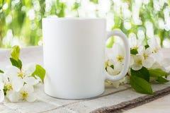 Maqueta de la taza con el flor de la manzana Foto de archivo