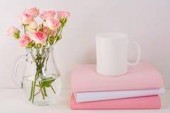Maqueta de la taza de café con las rosas rosadas Foto de archivo