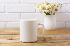Maqueta de la taza del café con leche con el ramo de la manzanilla en florero rústico imagen de archivo