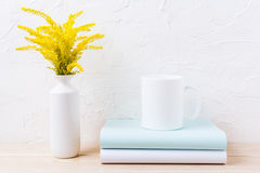 Maqueta de la taza del café con leche con la hierba floreciente amarilla ornamental Imagen de archivo libre de regalías