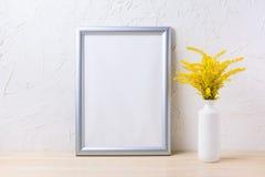 Maqueta de plata del marco con la hierba floreciente amarilla ornamental en el va Fotos de archivo libres de regalías