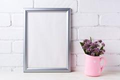 Maqueta de plata del marco con las flores púrpuras en jarra rústica rosada Imagenes de archivo
