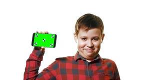 Maqueta del concepto Muchacho alegre que sostiene un smartphone en su mano con una pantalla verde Está en un fondo blanco metrajes