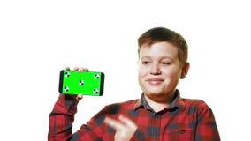 Maqueta del concepto Muchacho alegre que sostiene un smartphone en su mano con una pantalla verde y risas metrajes