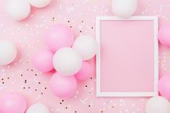 Maqueta del cumpleaños con el marco, los globos en colores pastel y el confeti en la opinión de sobremesa rosada Composición plan imágenes de archivo libres de regalías
