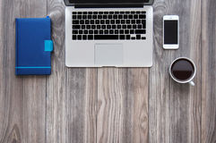 Maqueta del escritorio de oficina de la visión superior con el ordenador portátil, el smartphone, el café y la libreta imagen de archivo libre de regalías