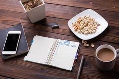 Maqueta del escritorio de oficina de la visión superior: ordenador portátil, smartphone, bocados, y taza de café Imágenes de archivo libres de regalías