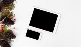 Maqueta del smartphone de la tableta para la Navidad ramas del abeto, conos y decoraciones de la Navidad en fondo de madera Opini Imagen de archivo