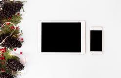 Maqueta del smartphone de la tableta para la Navidad ramas del abeto, conos y decoraciones de la Navidad en fondo de madera Opini Fotografía de archivo