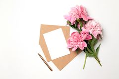 Maqueta del sobre horizontal del arte del negocio con una hoja del Libro Blanco con el ramo de peonías hermosas en un fondo gris imagenes de archivo