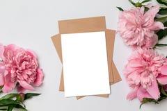 Maqueta del sobre horizontal del arte del negocio con una hoja del Libro Blanco con el ramo de peonías hermosas en un fondo gris fotografía de archivo