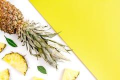 Maqueta del verano con la piña en la opinión superior del fondo amarillo y blanco Fotos de archivo