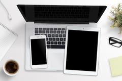 Maqueta elegante del teléfono y de la tableta en el teclado del ordenador portátil Concepto del escritorio de oficina fotografía de archivo libre de regalías