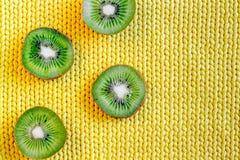 Maqueta exótica de la fruta con el kiwi cortado en la opinión superior del fondo amarillo de la tela Fotos de archivo