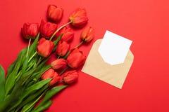 Maqueta minimalista con los tulipanes rojos, flor, sobre de la tarjeta del arte foto de archivo