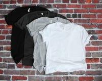 Maqueta negra, gris, y blanca de la camiseta en fondo del ladrillo foto de archivo libre de regalías
