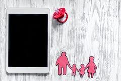 Maqueta para el concepto de la adopción PC cerca del pacificador del bebé, silueta de papel de la familia en copyspace ligero de  Fotos de archivo